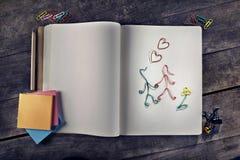 Mensajes adaptables del amor con los amantes hechos de los clips de papel en el cuaderno del vintage Imagenes de archivo