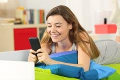 Mensajes adolescentes de la lectura en el teléfono en la cama Foto de archivo libre de regalías