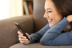 Mensajes de la lectura de la muchacha en un teléfono móvil en casa Imagenes de archivo