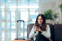 Mensajes de teléfono de la lectura de la mujer en sala de espera del aeropuerto imagen de archivo libre de regalías