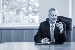 Mensajes de texto de la lectura del hombre de negocios en su teléfono imagen de archivo
