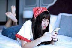 Mensajes de texto de la lectura de la muchacha en los teléfonos celulares Foto de archivo libre de regalías