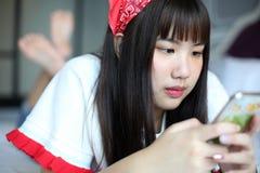 Mensajes de texto de la lectura de la muchacha en los teléfonos celulares Fotografía de archivo libre de regalías