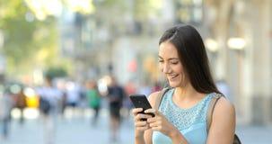 Mensajes que mandan un SMS de la muchacha en el teléfono en la calle almacen de video