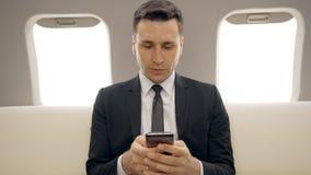 Mensajes que mecanografían del hombre de negocios acertado en su avión del teléfono móvil en privado almacen de metraje de vídeo