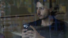 Mensajes que mecanografían del muchacho en su smartphone que se sienta en amigos que esperan solos de un pub para venir almacen de video