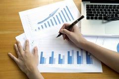 Mensch übergibt die Behälter- und Markierungsdiagramme, die in den documen überwachen Lizenzfreies Stockfoto