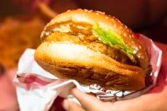 Mensch hält Burger mit den Händen Kosten oben lizenzfreie stockfotografie