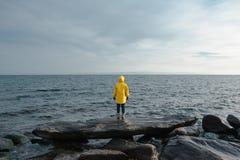 Mensch im gelben Regenmantelstand vor Meer Stockfoto