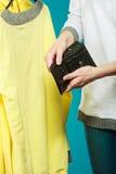 Mensch mit leerem Geldbörsengeldbeutel Frustrierte junge Frau, die ihren leeren Geldbeutel bei der Stellung lokalisiert auf Weiß  Lizenzfreie Stockfotos