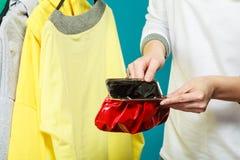 Mensch mit leerem Geldbörsengeldbeutel Frustrierte junge Frau, die ihren leeren Geldbeutel bei der Stellung lokalisiert auf Weiß  Lizenzfreies Stockfoto