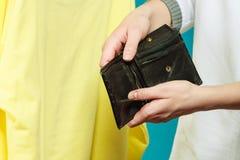 Mensch mit leerem Geldbörsengeldbeutel Frustrierte junge Frau, die ihren leeren Geldbeutel bei der Stellung lokalisiert auf Weiß  Lizenzfreie Stockbilder