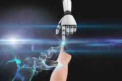 Mensch und Roboter, die ihre Finger gegen schwarzen Hintergrund berühren Lizenzfreie Stockbilder