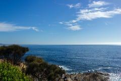 2 Menschen auf einer Küstenlinie mit Ozean und Felsen, Australien lizenzfreie stockfotos