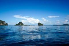 3 Menschen, die auf dem blauen Meer Kayak fahren Stockfotografie