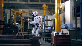 Menschlich ähnlicher Cyborg benutzt eine Tablette in den Fabrikvoraussetzungen stock video