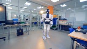 Menschlich ähnlicher Cyborg bewegt seine Hand wellenartig, um jemand zu grüßen stock video