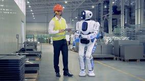 Menschlich ähnlicher Cyborg erhält sich anschaltete und Einrichtung durch einen männlichen Arbeiter stock video footage