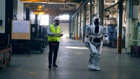 Menschlich ähnlicher Cyborg und ein männlicher Techniker gehen stock video