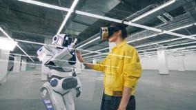 Menschlich ähnlicher Roboter berührt eine Hand einer Frau in den VR-Gläsern stock footage