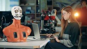 Menschlich ähnlicher Roboter bewegt seinen Mund unter Steuerung einer jungen Frau stock footage