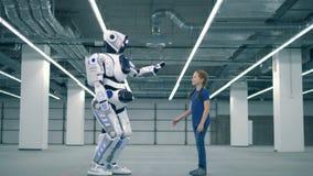Menschlich ähnlicher Roboter gibt einem kleinen Mädchen ein hoch--fünf stock video footage