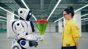 Menschlich ähnlicher Roboter gibt einer jungen Frau Blumen stock video