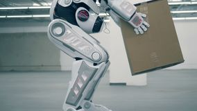 Menschlich ähnlicher Roboter hebt einen Kasten an und trägt ihn stock footage