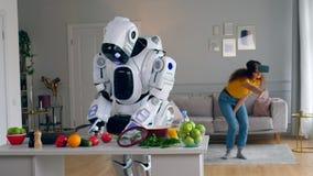 Menschlich ähnlicher Roboter kocht mit einer Dame in den VR-Gläsern, die nahe ihm sich bewegen stock video