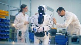 Menschlich ähnlicher Roboter läuft einen Festlegungsverfahrensgriff durch zwei Techniker durch stock video