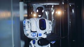 Menschlich ähnlicher Roboter steht mit einem Laptop in einem Serverraum stock footage