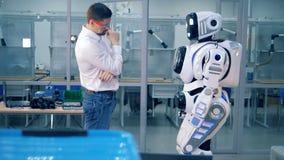 Menschlich ähnlicher Roboter wird indem einen männlichen Ingenieur und das Gehen zurück zu ihm weggedrückt stock video