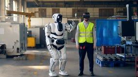 Menschlich ähnliches droid bewegt sich nach einer Arbeitskraft in den VR-Gläsern stock footage