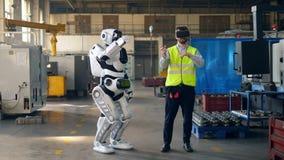 Menschlich ähnliches droid bewegt sich unter Steuerung der Arbeitskraft in den VR-Gläsern stock video