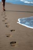 Menschliche Abdrücke auf dem Sand zum Meer Stockfotos