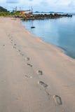 Menschliche Abdrücke auf dem sandigen Strand zur Sonnenuntergangzeit Stockbilder