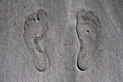 Menschliche Abdrücke auf Strandsand, Abschluss oben lizenzfreie stockfotografie