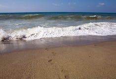Menschliche Abdrücke führen zu das rasende Meer Stockfotos