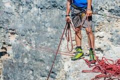 Menschliche Beine auf Klippe mit Seil Lizenzfreies Stockfoto