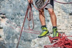 Menschliche Beine auf Klippe mit Seil Lizenzfreie Stockbilder