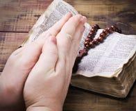 Menschliche die Bibel anhaltene und betende Hände stockfoto