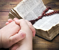 Menschliche die Bibel anhaltene und betende Hände stockfotos