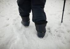 Menschliche Füße Filzstiefel in den Gummis tragend, die auf Schnee gehen lizenzfreie stockfotografie