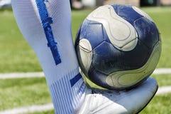 Menschliche Fahrwerkbein- und Fußballkugel Lizenzfreie Stockfotos