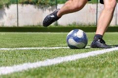 Menschliche Fahrwerkbeinschießen-Fußballkugel Stockfoto