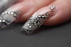 Menschliche Finger mit dem langen Fingernagel Stockfotografie