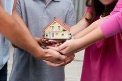 Menschliche Hände, die ein Baumuster des Hauses anhalten Stockbild