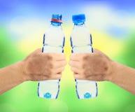 Menschliche Hände, die Flaschen Wasser auf dem Naturhintergrund halten Stockfotografie