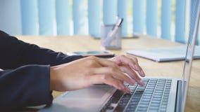 Menschliche Hände, die an Laptop auf Bürohintergrund arbeiten Eine junge Frau in den Büroskala ein Dokument auf der Tastatur stock footage