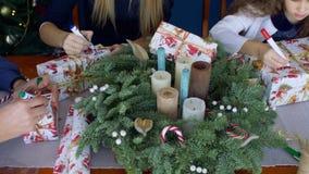 Menschliche Hände, die Namen auf Weihnachtsgeschenke schreiben stock footage